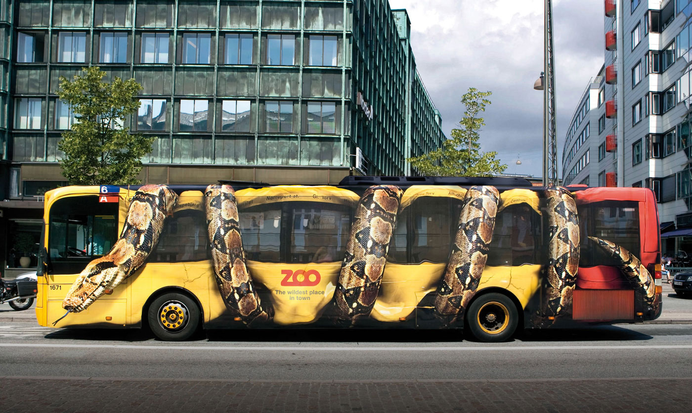 Giant constrictor snake squeezing complete Copenhagen citybus.